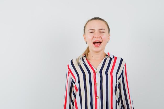 Giovane donna che chiude gli occhi e cerca di urlare in camicetta a righe e sembra infastidita