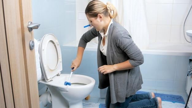 トイレを洗ったり掃除したりしながら、洗濯バサミで鼻を閉じる若い女性。