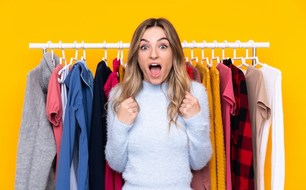 Young woman in a clothing store over isolated yellow wall celebrating a victory