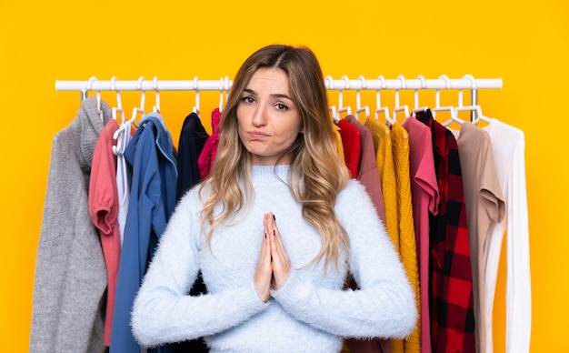 Young woman in a clothing store over isolated yellow wall pleading