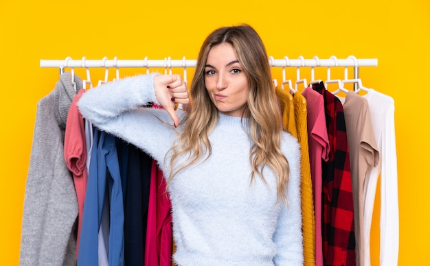 Young woman in a clothing store over isolated yellow wall showing thumb down sign