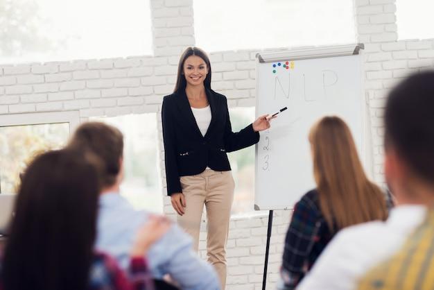 Young woman coacher is conducting seminar.