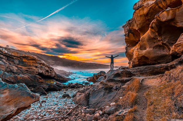 A young woman on the coast of jaizkibel and the geoforms near san sebastian. basque country