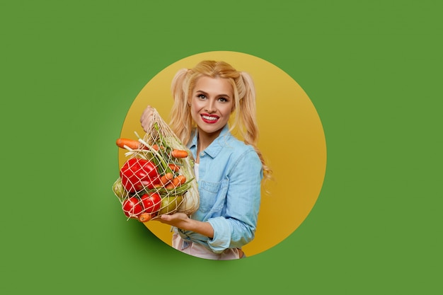 Young woman collected fresh vegetables in a string bag on a green background. peeks out of a round hole in the wall.