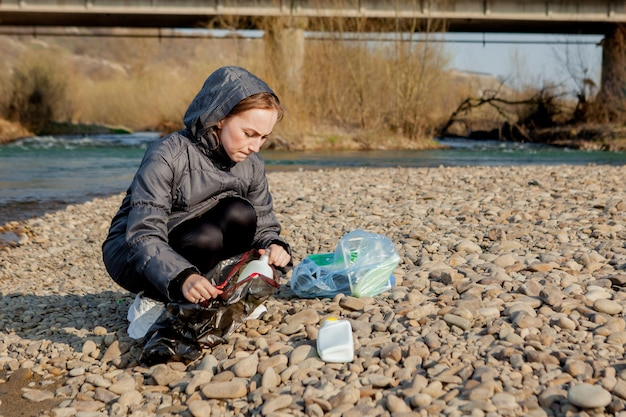 Young woman collecting plastic trash from the beach and putting it into black plastic bags for recycle. cleaning and recycling concept.