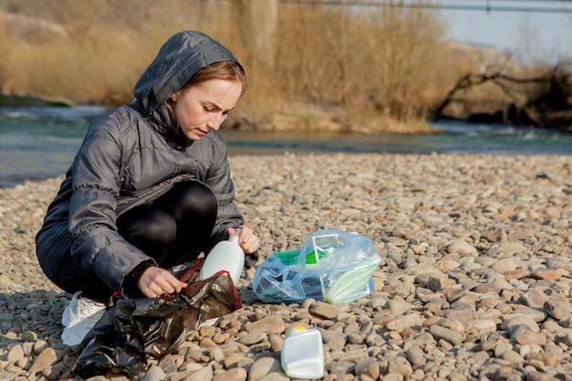 Молодая женщина собирает пластиковый мусор с пляжа и складывает его в черные пластиковые пакеты для переработки