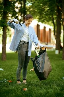 Молодая женщина собирает мусор в полиэтиленовый пакет в парке, волонтерство