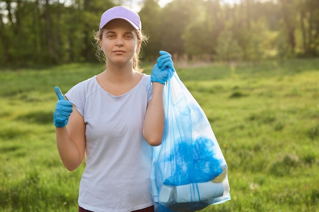 Young woman collects garbage out from grasses in garden