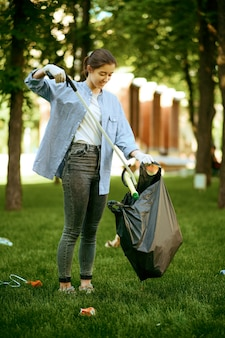 Young woman collects garbage in plastic bag in park, volunteering