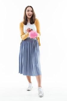 Молодая женщина собирает деньги в розовую копилку