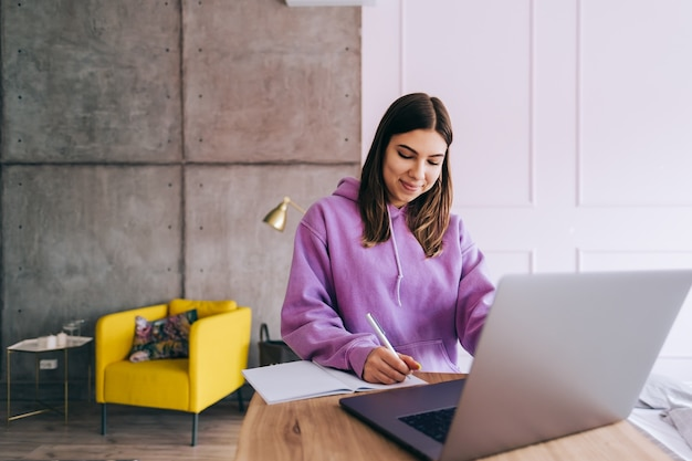 ラップトップで勉強している若い女性の大学生、遠方でテスト試験の準備、自宅で宿題をしているエッセイを書いている、遠方の教育の概念。