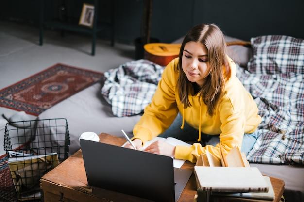 ノートパソコンで勉強し、遠方で試験の準備をし、自宅で宿題をするエッセイを書く若い女性大学生