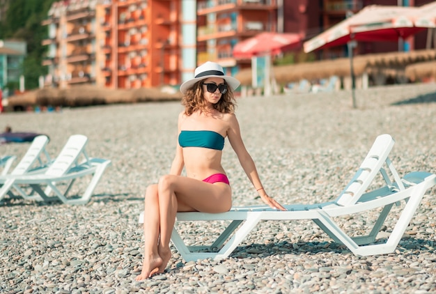 Young woman in color bikini enjoying the summer with copy space. woman sunbathing at seaside. summer vacation, holidays, relax. deck chairs, umbrellas