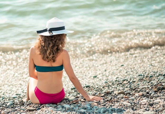 Young woman in color bikini and white hat enjoying the summer with copy space. woman sunbathing at seaside. summer vacation, holidays, relax. pebble stone shore