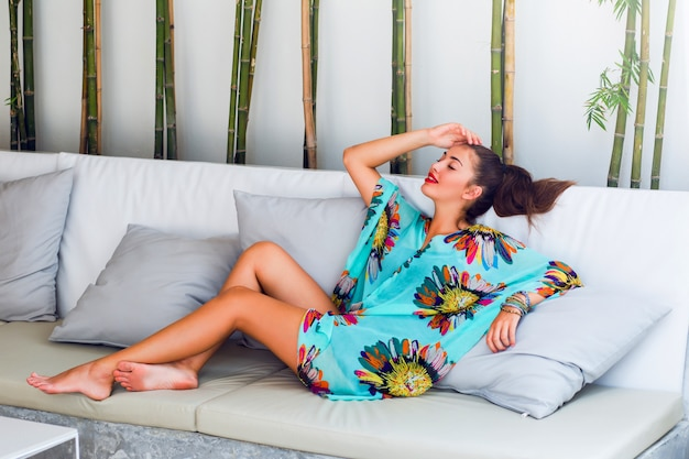 Young woman in colorful boho outfit relaxing on white sofa