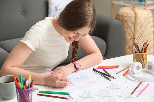 집에서 그림을 색칠하는 젊은 여자