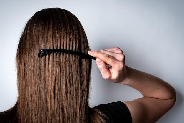 그녀의 머리를 빗질하는 젊은 여자.