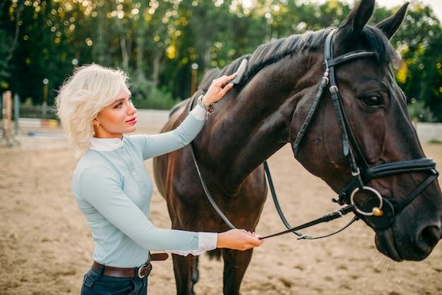Молодая женщина, расчесывающая гриву лошади