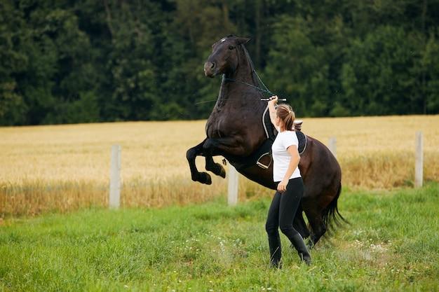 Молодая женщина командует лошадью