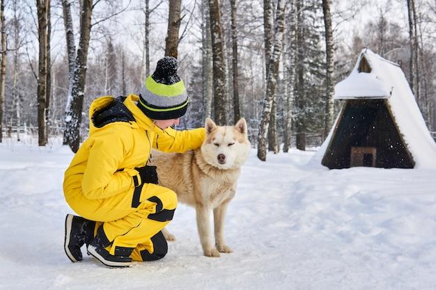 Молодая женщина общается с хаски в зимнем лесу