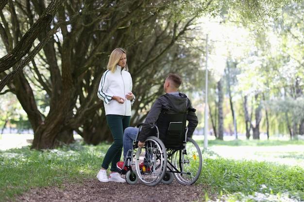 Молодая женщина общается с мужчиной в инвалидной коляске в парке поддержки людей с ограниченными возможностями