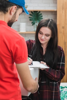 Young woman confirming parcel reception