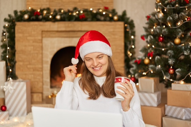 Young woman congratulating with christmas her close people while sitting on floor in front of tree with her laptop, having happy expression, touching her pom pom from santa hat.