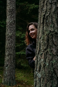 A young woman in a coniferous forest looks out from behind a tree. happy young woman