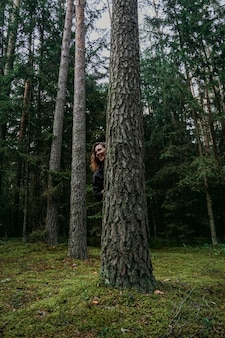 A young woman in a coniferous forest looks out from behind a tree