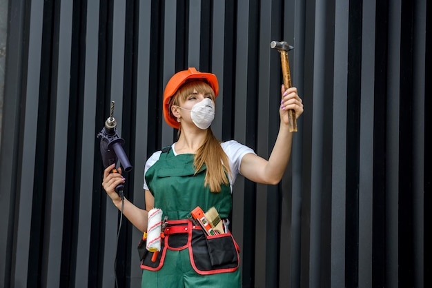 Young woman in construction clothes and protective equipment posing with a drill and hammer on grey wall.