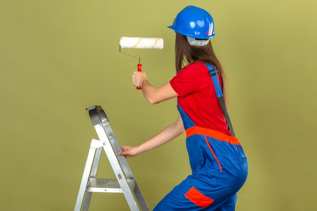 Young woman in construction uniform and blue safety helmet on ladder holding paint roller on green background