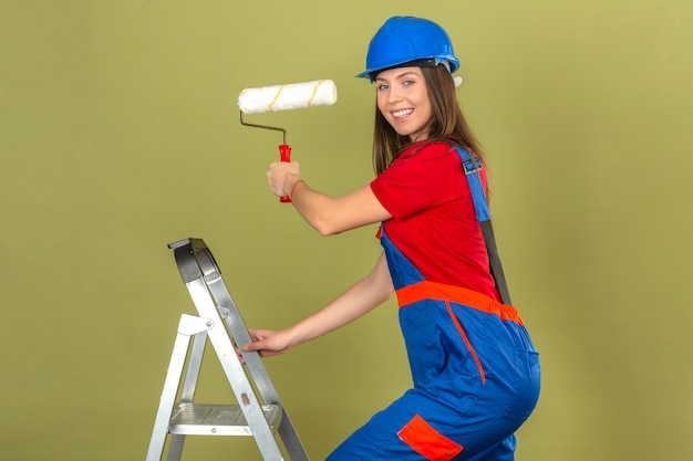 Young woman in construction uniform and blue safety helmet on ladder smiling and holding paint roller on green background
