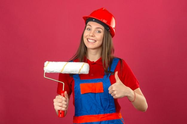 Giovane donna in uniforme di costruzione e casco di sicurezza rosso che sorride mostrando segno giusto e tenendo il rullo di vernice su sfondo rosa scuro
