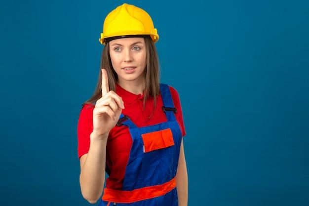 Giovane donna in uniforme di costruzione e casco di sicurezza giallo che indica su con la condizione sorridente del dito sul fondo blu