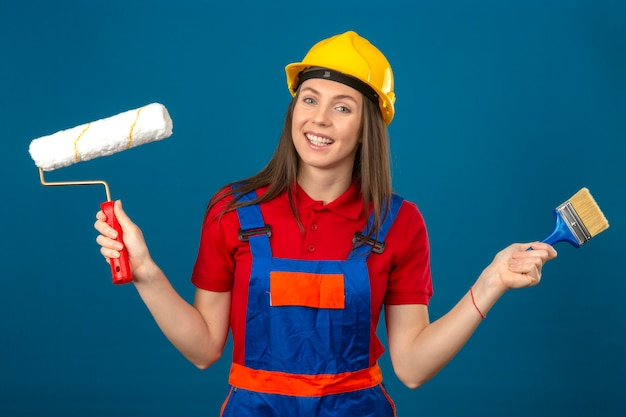 La giovane donna in uniforme da costruzione e casco di sicurezza giallo sorridenti che tengono il rullo e la spazzola di pittura in mani che stanno sul fondo isolato blu Foto Gratuite