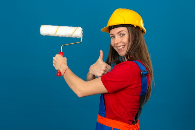 Young woman in construction uniform and yellow safety helmet smiling showing thumb up and holding paint roller in hand on blue isolated background