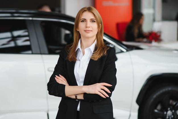 Молодая женщина-консультант в выставочном зале, стоя возле автомобиля