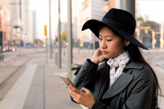 Молодая женщина консультируется с мобильным телефоном в ожидании трамвая