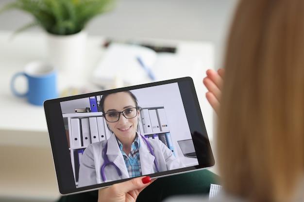 Молодая женщина консультируется с семейным терапевтом онлайн-видеозвонком на планшете медицинскому работнику
