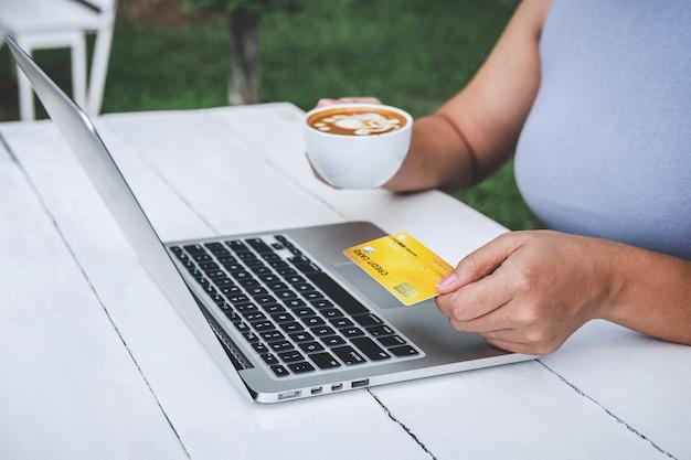 若い女性消費者がクレジットカードを保持し、オンラインショッピングや支払いのためにラップトップに入力