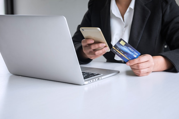Young woman consumer holding smartphone, credit card and typing on laptop for online shopping and payment make a purchase on the internet, online payment, networking and buy product technology