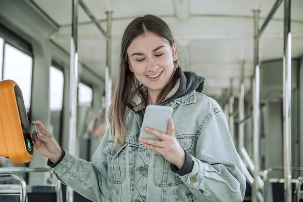 A young woman contactless pays for public transport.