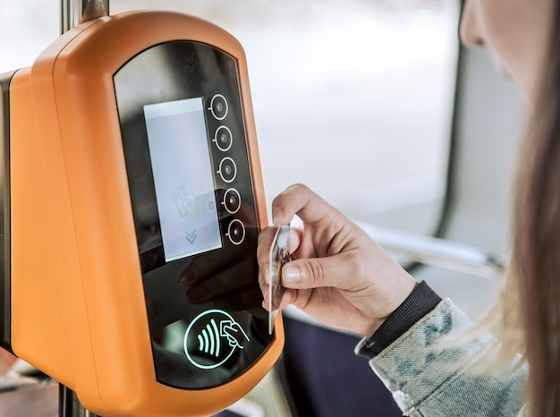 A young woman contactless pays for public transport
