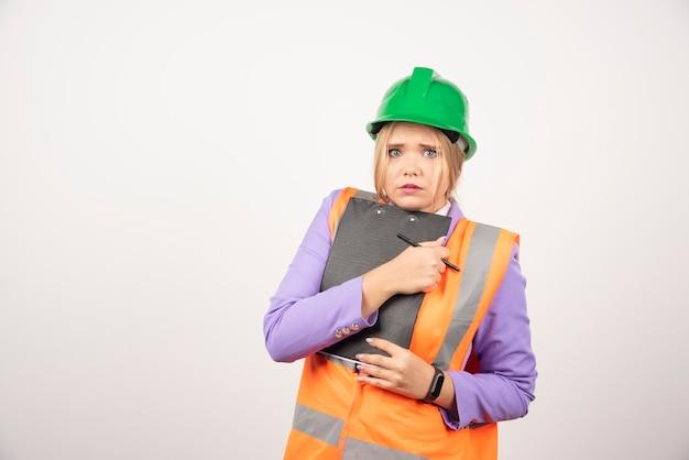 緑のヘルメットと白のクリップボードを持つ若い女性請負業者。