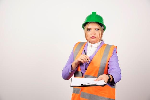 Appaltatore della giovane donna con il casco e la lavagna per appunti verdi su bianco.