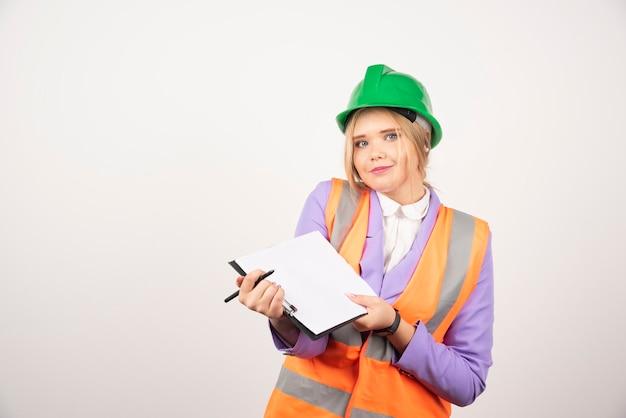 L'appaltatore della giovane donna con il casco verde ha aperto la lavagna per appunti su bianco.