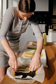 若い女性が台所で甘いケーキを調理