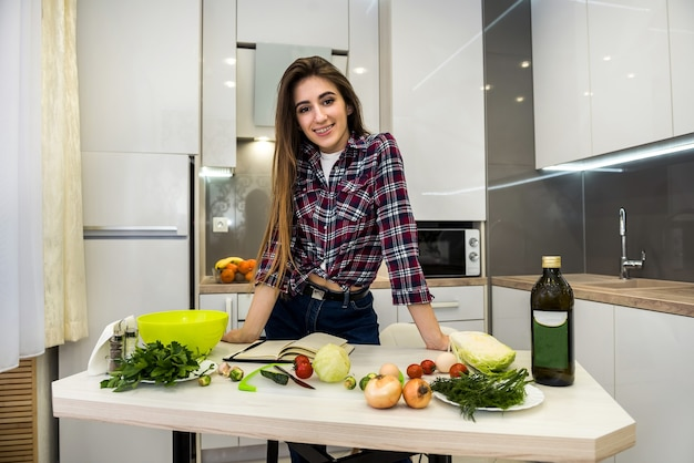 彼女の台所の助けとしてメモ帳を使用して食べ物を調理する若い女性。