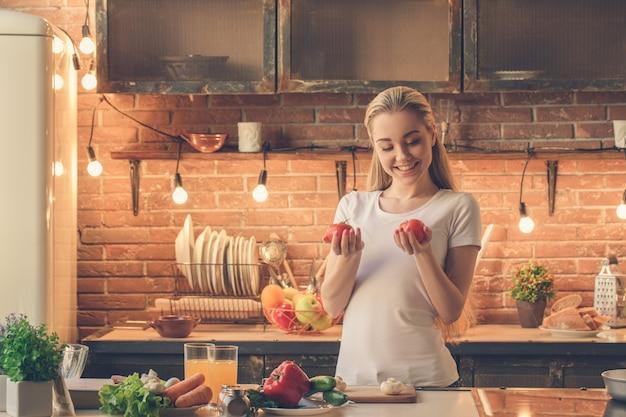 家で健康的な新鮮な食事を調理する若い女性