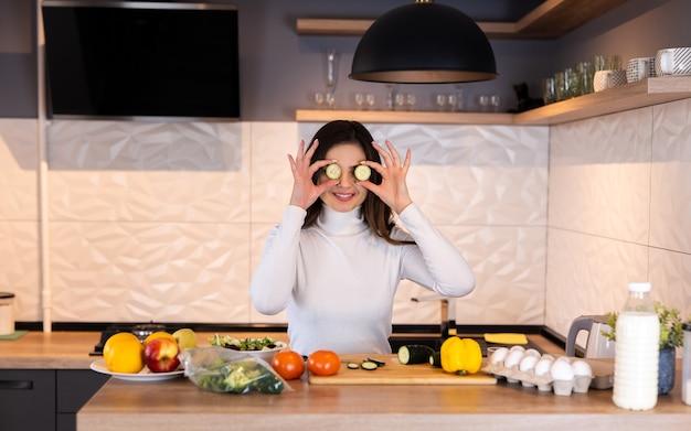 台所で料理をしている若い女性。楽しんでください。健康食品。ダイエットの概念。健康的な生活様式。家庭での料理。食べ物を用意します。
